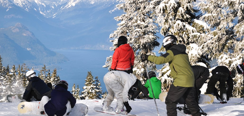 group of snowboarders on mountain top